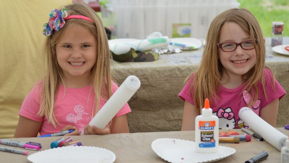 These are two girls making arts and crafts.