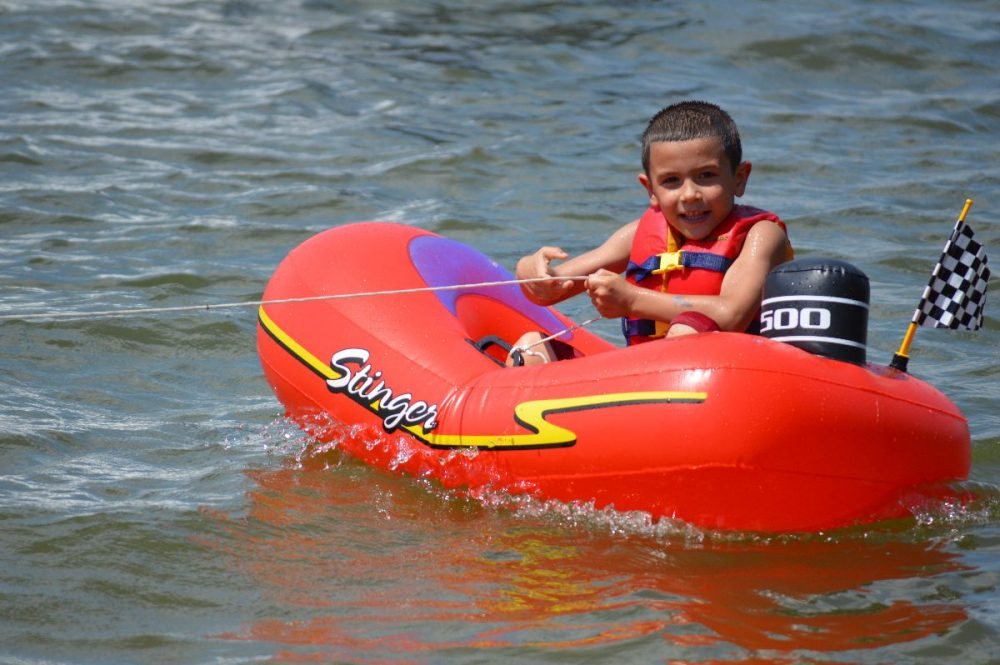 This is a young boy tubing on the lake.