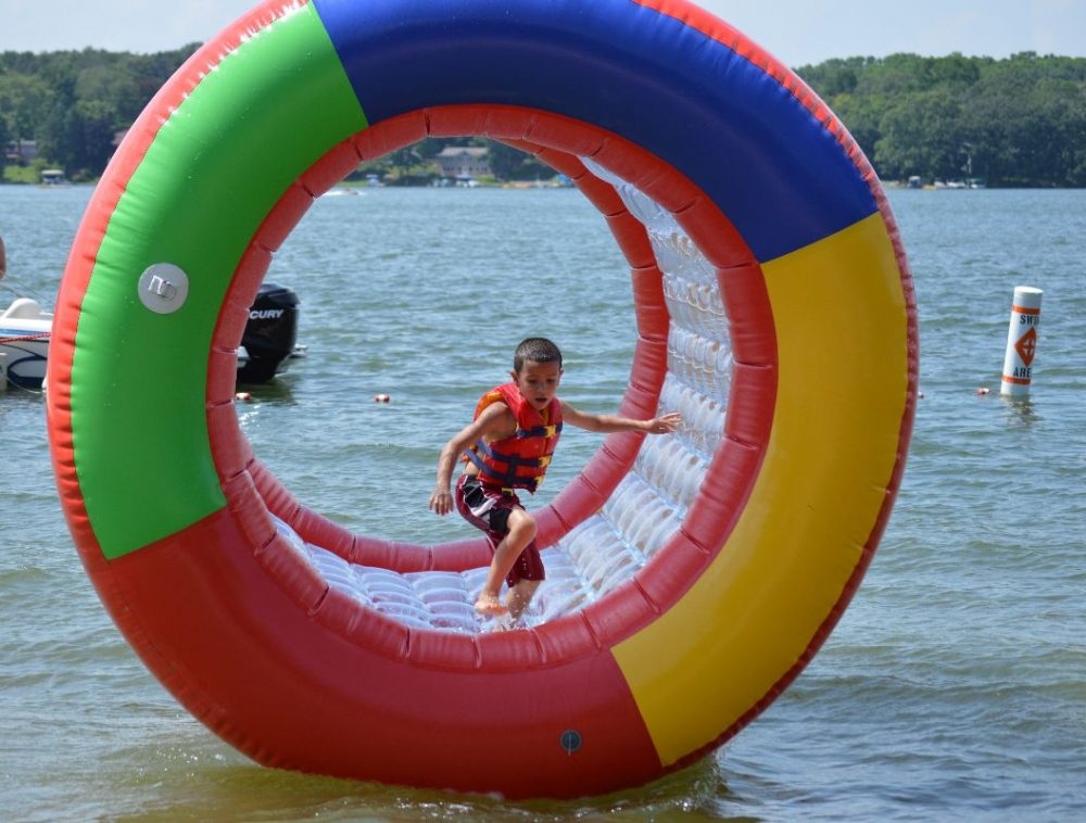 This is a young boy playing in an inflatable wheel on the lake.