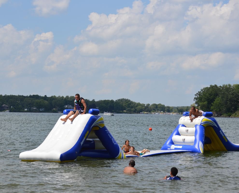 These are campers playing on inflatable slides in the lake.