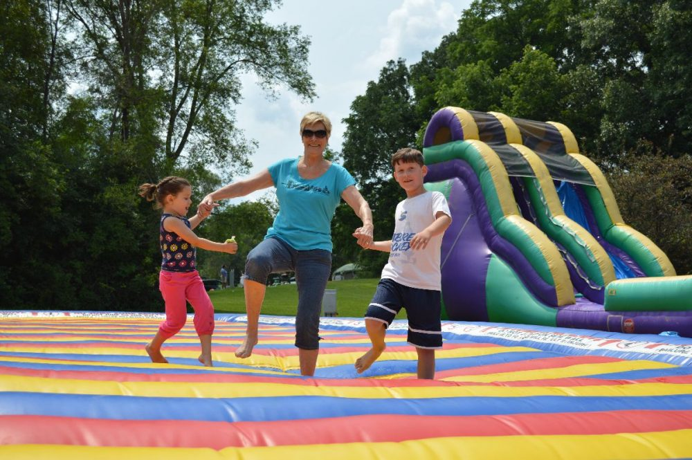 This is a mom and here kids bouncing on the inflatable mat.