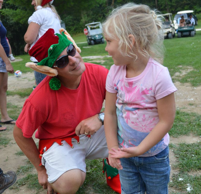 This is a young girl and a man dressed as a Christmas elf.