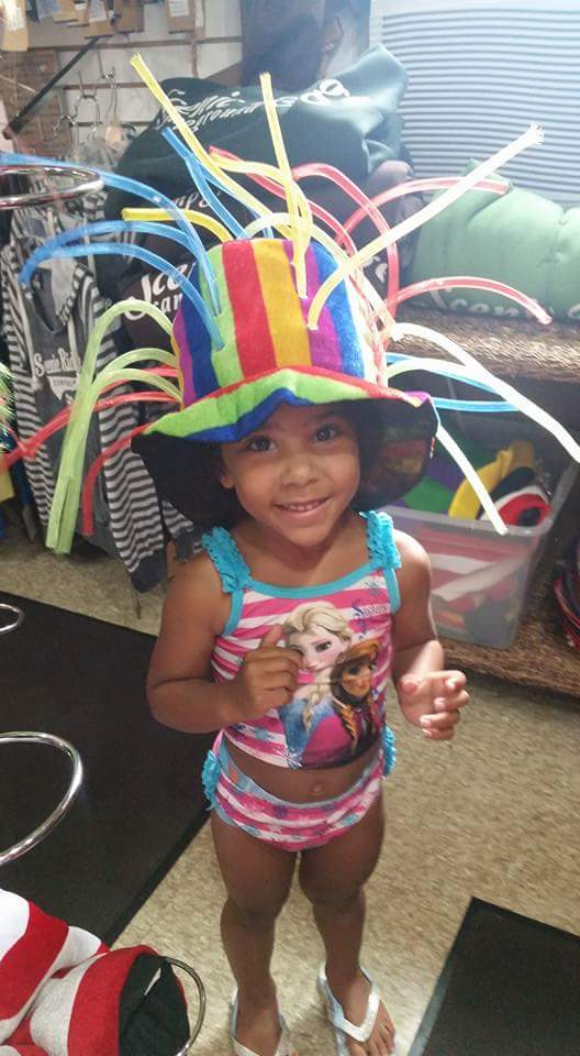 This is a young girl wearing a crazy hat.