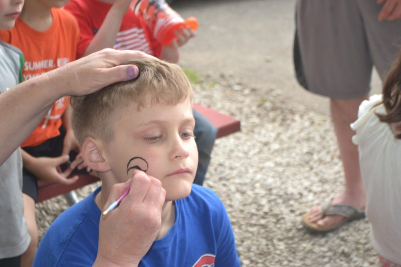 This is an image of a kid getting his face painted.